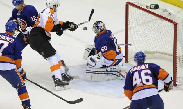 Philadelphia Flyers' Vincent Lecavalier (40) shoots the puck past New York Islanders' Josh Bailey (12) and goalie Kevin Poulin (60) to score his second goal in the first period of an NHL hockey game at the Nassau Coliseum on Saturday, Oct. 26, 2013, in Uniondale, N.Y. (AP Photo/Kathy Kmonicek)