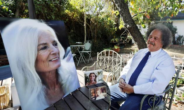 ADVANCE FOR USE SUNDAY, MAY 11, 2014 AND THEREAFTER - In this Wednesday, Feb. 19, 2014 photo, Jay Westbrook, clinical director of Compassionate Journey, sits next to photos of his late wife, Nancy, in their backyard in Los Angeles. There have been thousands of souls he journeyed with to the intersection of living and dying, who helped establish him as one of the foremost experts on hospice care. Then came one death too many - when his beloved Nancy died. (AP Photo/Damian Dovarganes)