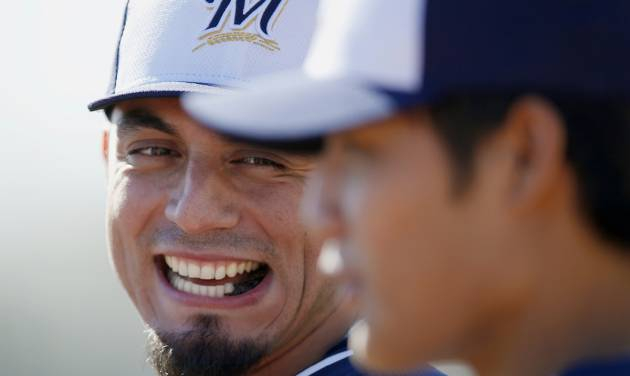 Milwaukee Brewers' Matt Garza, left, laughs as he tries to talk to teammate Wei-Chung Wang, of Taiwan, during spring training baseball practice, Monday, Feb. 17, 2014, in Phoenix. (AP Photo/Ross D. Franklin)