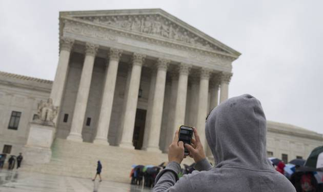 "FILE - This April 29, 2014 file photo shows a visitor to the Supreme Court uses his cellphone to take a photo of the court in Washington. A divided Supreme Court sided with gun control groups and the Obama administration Monday, ruling that the federal ban on ""straw"" purchases of guns can be enforced even if the ultimate buyer is legally allowed to own a gun. The justices ruled 5-4 that the law applied to a Virginia man who bought a gun with the intention of transferring it to a relative in Pennsylvania who was not prohibited from owning firearms. (AP Photo, File)"