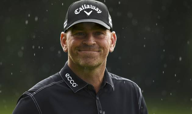 Denmark's Thomas Bjorn  smiles in the rain on the 18 green during day one of the  BMW PGA Championship at the Wentworth Club,  Virginia Water England Thursday May 22, 2014. Bjorn shot a 10-under-par 62 in the first round.(AP PhotoAdam Davy/PA) UNITED KINGDOM OUT