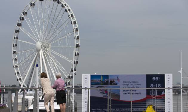 This photo taken May 20, 2014 shows a new Ferris wheel overlooking Washington at National Harbor in Oxon Hill, Md. With a massive new Ferris wheel overlooking the nation's capital, a children's museum, a village of restaurants and hotels and a major casino resort on the horizon, National Harbor in Maryland has quickly become a travel alternative to the marble monuments and museums of nearby Washington. (AP Photo/ Evan Vucci)