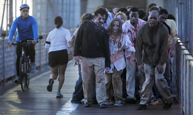 """A bicyclist and jogger pass a group of  zombies posing for pictures on the Brooklyn Bridge in  New  York, Tuesday, Oct. 26, 2010. The stunt was part of a campaign in 26  cities worldwide promoting the Halloween premiere of the AMC television series """"The Walking Dead."""""""