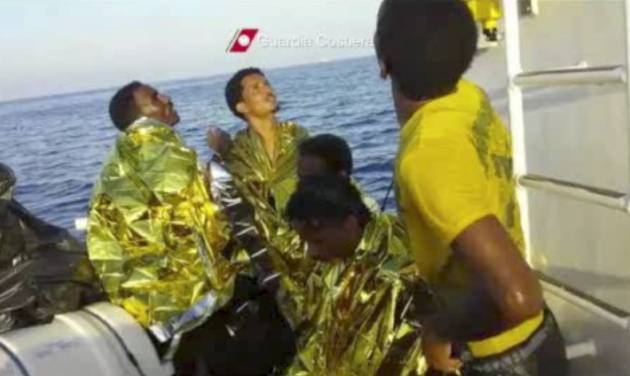 In this image made from video provided by the Italian Coast Guard and recorded on Thursday, Oct. 3, 2013, survivors of a ship transporting hundreds of migrants which caught fire and sank wear thermal rescue blankets after being rescued by the Italian Coast Guard off the Sicilian island of Lampedusa, Italy. Authorities on Friday, Oct. 4 are contending with choppy waters in the search for dozens of migrants believed to have drowned after their rickety boat caught fire and sank off the coast of the southern Italian island of Lampedusa. (AP Photo/Italian Coast Guard)