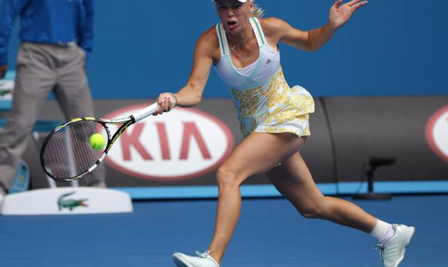 Caroline Wozniacki of Denmark makes a forehand return to Garbine Muguruza of Spain during their third round match at the Australian Open tennis championship in Melbourne, Australia, Saturday, Jan. 18, 2014.(AP Photo/Aaron Favila)