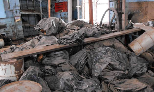 This photo taken on March 3, 2014, and provided by the North Dakota Health Department, shows bags full of radioactive oil filter socks, the nets that strain liquids during the oil production process, piled in an abandoned building in Noonan, North Dakota.  State Waste Management Director Scott Radig said the hundreds of the tubular filters discovered last week in the abandoned building is likely to be more than twice as large as the state's next-largest dumping incident found last month in McKenzie County. (AP Photo/North Dakota Health Department)
