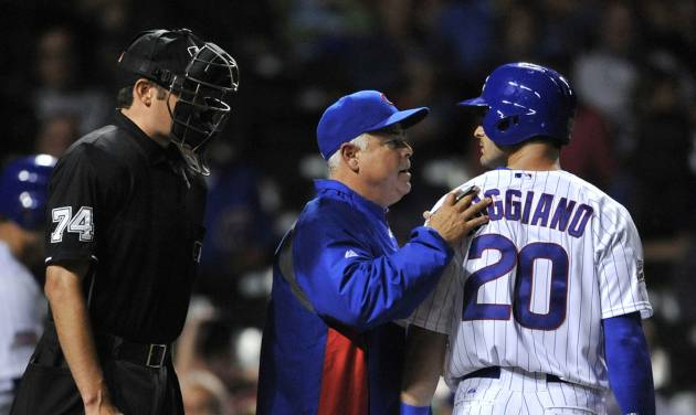 Chicago Cubs' Justin Ruggiano (20) is held back by Cubs manager Rick Renteria center, while home plate umpire John Tumpane (74) watches after Ruggiano struck out during the eighth inning of a baseball game against the Pittsburgh Pirates in Chicago, Saturday, June 21, 2014. (AP Photo/Paul Beaty)