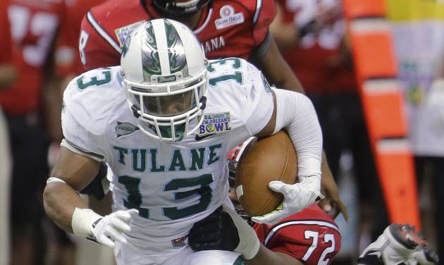 Tulane cornerback Derrick Strozier (13) is stopped by Louisiana-Lafayette offensive linesman Terry Johnson (72) during the second half of the New Orleans Bowl NCAA college football game in New Orleans, Saturday, Dec. 21, 2013.  (AP Photo/Bill Haber)