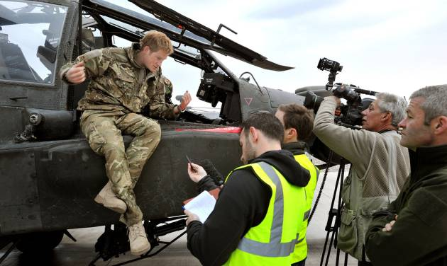FILE - In this Dec. 12, 2012 file photo, Britain's Prince Harry talks to a TV crew after making his early morning pre-flight checks on the flight line, at Camp Bastion southern Afghanistan. During Prince Harry's 20-week deployment in Afghanistan, he served as an Apache helicopter pilot with the Army Air Corps. (AP Photo/John Stillwell, Pool, File)