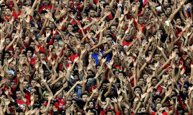 Egyptian club Al Ahly fans cheer during the African Champions League second leg final match between Egyptian Al Ahly club and South Africa's Orlando Pirates, at the Arab Contractors stadium in Cairo, Egypt, Sunday, Nov. 10, 2013. Hundreds of Egyptian soccer fans have clashed with police outside a Cairo stadium before the African Champions League final. (AP Photo/Osama Abdel Naby)