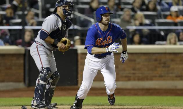 Atlanta Braves catcher Gerald Laird, left, joins New York Mets' Ike Davis as they watch Davis's eighth-inning, two-run, single in the Mets 4-2 victory during a baseball game at Citi Field in New York, Sunday, May 26, 2013. (AP Photo/Kathy Willens)
