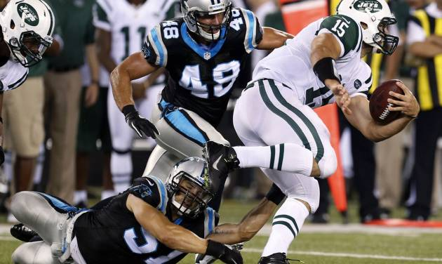 New York Jets quarterback Tim Tebow (15) avoids tackles from Carolina Panthers' Jordan Senn (57) and J.J. Finley (49) during the second half of a preseason NFL football game Sunday, Aug. 26, 2012, in East Rutherford, N.J. (AP Photo/Julio Cortez)