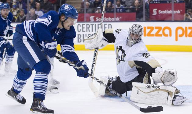 Toronto Maple Leafs forward James van Riemsdyk, left, gets stopped by Pittsburgh Penguins goalie Marc-Andre Fleury, right, during the second period of an NHL hockey game, Saturday, Oct. 26, 2013 in Toronto. (AP Photo/The Canadian Press, Nathan Denette)
