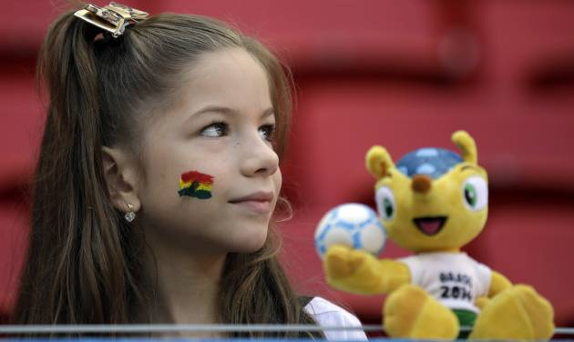 A young girl waits with the mascot 'Fuleco' for the start of the group G World Cup soccer match between Portugal and Ghana at the Estadio Nacional in Brasilia, Brazil, Thursday, June 26, 2014. (AP Photo/Martin Mejia)