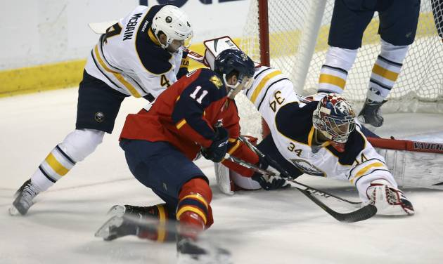 Florida Panthers' Jonathan Huberdeau (11) tries to score as Buffalo Sabres goalie Michael Neuvirth (34) and Jamie McBain (4) try to block the shot during the first period of an NHL hockey game in Sunrise, Fla., Friday, March 7, 2014. (AP Photo/J Pat Carter)