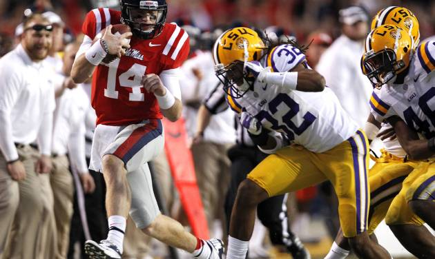 Mississippi quarterback Bo Wallace (14) carries as LSU cornerback Jalen Collins (32) pursues in the second half of their NCAA college football game in Baton Rouge, La., Saturday, Nov. 17, 2012. LSU won 41-35. (AP Photo/Gerald Herbert)