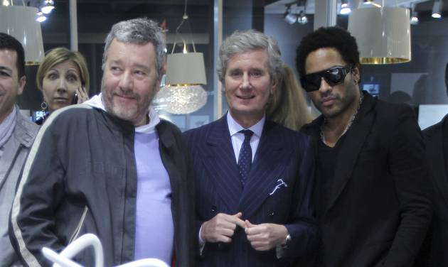 French designer Philippe Starck, left, Kartell Home furniture company CEO Claudio Luti, center, and US rock star Lenny Kravitz look at chairs at the Kartell Home company space during Milan's Furnishing Accessories Exhibition, in Milan, Italy, Tuesday, April 17, 2012. The Milan furniture fair, a six-day event which ended Sunday, was full of experiment and whimsy. (AP Photo/Antonio Calanni)