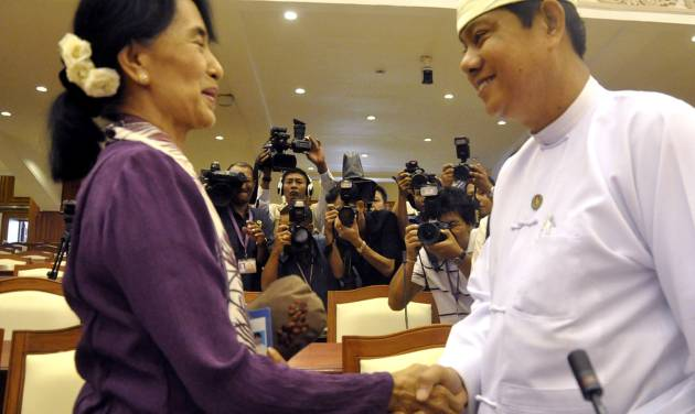 Myanmar opposition leader Aung San Suu Kyi, left, shakes hands with Htay Oo, right, general secretary of Union Solidarity and Development party headed by President Thein Sein, as she attends a regular session of Myanmar Lower House in Naypyitaw, Myanmar, Wednesday, May 2, 2012. Suu Kyi was sworn in to Myanmar's military-backed parliament Wednesday, taking public office for the first time since launching her struggle against authoritarian rule nearly a quarter century ago. (AP Photo/Khin Maung Win)