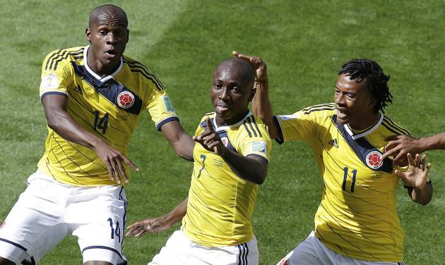 Colombia's Pablo Armero, center, celebrates with teammates, Victor Ibarbo, left, and Juan Cuadrado, right, after scoring during the group C World Cup soccer match between Colombia and Greece at the Mineirao Stadium in Belo Horizonte, Brazil, Saturday, June 14, 2014.  (AP Photo/Andrew Medichini)