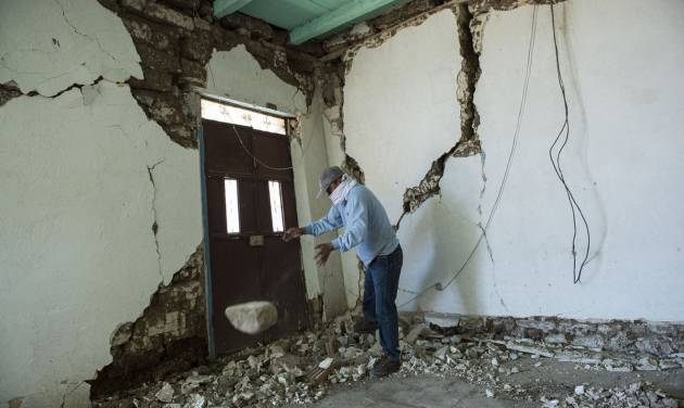 Mynor Fuentes checks his home after it was damaged during an earthquake in San Pedro, Guatemala, Monday, July 7, 2014. A magnitude-6.9 earthquake on the Pacific Coast jolted a wide area of southern Mexico and Central America Monday. (AP Photo/Oliver de Ros)