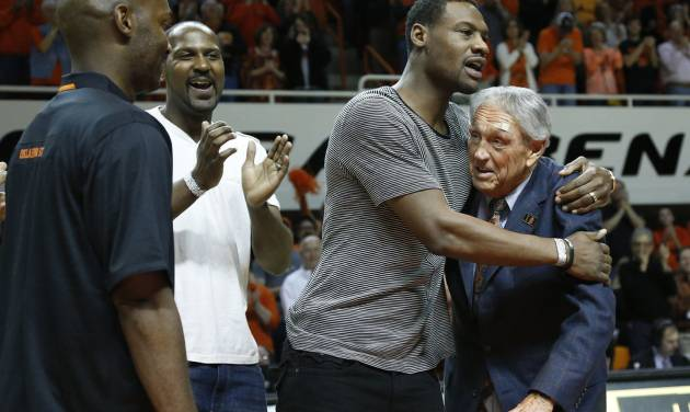 Former Oklahoma State basketball player Tony Allen, second from right, hugs former head coach Eddie Sutton, right, during ceremonies in honor of the 2004 OSU team which reached the Final Four, during halftime of an NCAA college basketball game between Oklahoma and Oklahoma State in Stillwater, Okla., Saturday, Feb. 15, 2014. Looking on at left are John Lucas III and Ivan McFarlin. (AP Photo/Sue Ogrocki)