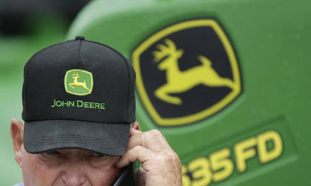 FILE - In this Sept. 11, 2014 file photo, a John Deere tractor is on display behind a man wearing a John Deere cap at the annual Husker Harvest Days agriculture fair in Grand Island, Neb. Deere & Company reports quarterly earnings on Wednesday, May 14, 2014.  (AP Photo/Nati Harnik, File)
