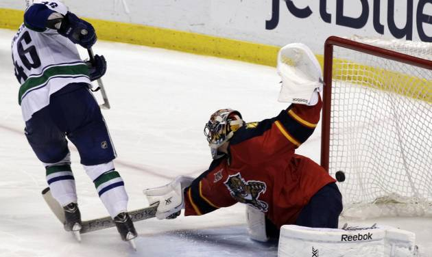 Vancouver Canucks'  Nicklas Jensen (46), of Denmark, scores the winning goal on Florida Panthers goalkeeper Roberto Luongo during a shootout of an NHL hockey game on Sunday, March 16, 2014, in Sunrise, Fla. The Canucks won 4-3 in a shootout. (AP Photo/Luis M. Alvarez)