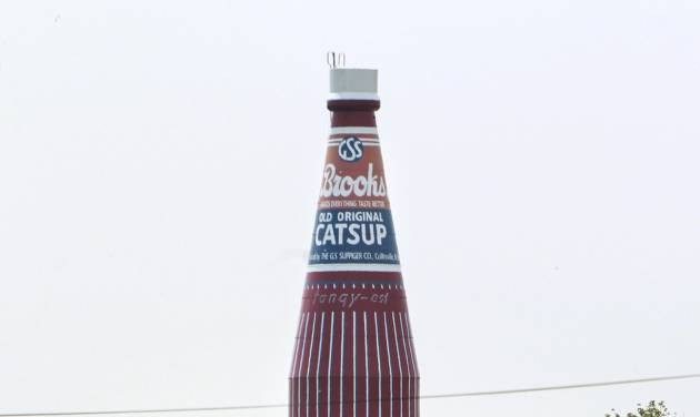 """A 170-foot giant ketchup bottle, billed as the """"World's Largest Bottle of Catsup,"""" and once served as a water tower is seen Tuesday, July 22, 2014, in Collinsville, Ill. A """"For Sale"""" has been placed in front of the landmark that replicates a bottle of Brooks Old Original Rich and Tangy Catsup, which was produced in the buildings beneath the tower. The 100,000-gallon tower held water _ never ketchup _ and hasn't been used since Brooks moved out in the early 1960s.  (AP Photo/Belleville News-Democrat, Derik Holtmann)"""