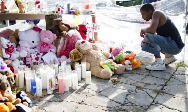 Richard Starchia pays his respects Monday, July 28, 2014, at a makeshift memorial for three children who were killed Friday by a hijacked car that lost control and hit a group of people in Philadelphia. Police investigators are talking to two people in connection with the search for two carjackers who rammed a stolen sport utility vehicle into a family in north Philadelphia, killing three children. (AP Photo/Matt Rourke)