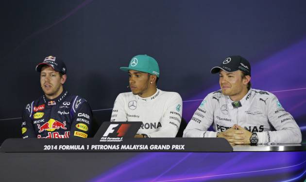 Red Bull Racing driver Sebastian Vettel, left, of Germany speaks as Mercedes drivers Lewis Hamilton, center, of Britain and Nico Rosberg, right, of Germany listen during a press conference after the qualifying session for Sunday's Malaysian Formula One Grand Prix at Sepang International Circuit in Sepang, Malaysia, Saturday, March 29, 2014. Hamilton took the pole position while Vettel with second position and Rosberg with third position. (AP Photo/Peter Lim)