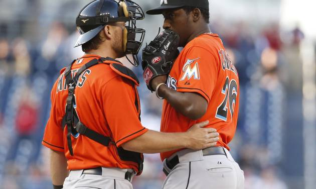 Miami Marlins catcher Jeff Mathis, left, talks with relief pitcher Arquimedes Caminero during the eighth inning of a baseball game against the Washington Nationals at Nationals Park, Thursday, April 10, 2014, in Washington. The Nationals won 7-1. (AP Photo/Alex Brandon)