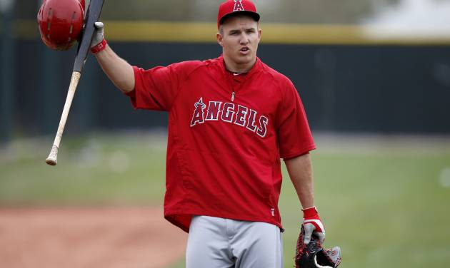 Los Angeles Angels' Mike Trout talks to a few teammates as he arrives to take batting practice during spring training baseball practice on Tuesday, Feb. 25, 2014, in Tempe, Ariz. (AP Photo/Ross D. Franklin)