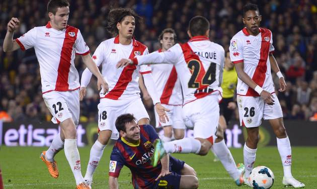 FC Barcelona's Lionel Messi, from Argentina, third left, duels for the ball against Rayo Vallecano's Iago Falque during a Spanish La Liga soccer match at the Camp Nou stadium in Barcelona, Spain, Saturday, Feb. 15, 2014. (AP Photo/Manu Fernandez)