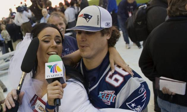"""File-This Jan. 29, 2008 file photo shows Ines Gomez Mont, a reporter from TV Azteca in Mexico, wearing a wedding dress as she is carried by New England Patriots center Lonie Paxton while interviewing him during media day for the Super Bowl XLII football game in Glendale, Ariz.  Once a serious endeavor, media day is now a forum for credentialed """"media"""" such as Mont. The entertainment reporter for Mexico's TV Azteca showed up in Glendale, Ariz., wearing a scanty white wedding dress and towering red pumps. She spent the next two hours trying to persuade someone, anyone, to accept her marriage proposal. (AP Photo/The Arizona Republic, Michael Chow, File)"""