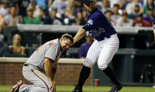 Colorado Rockies relief pitcher Tommy Kahnle (54) applies a late tag to the face of Washington Nationals' Ryan Zimmerman (11)  during the seventh inning of a baseball game on Monday, July 21, 2014, in Denver. Zimmerman scored on the play. (AP Photo/Jack Dempsey)