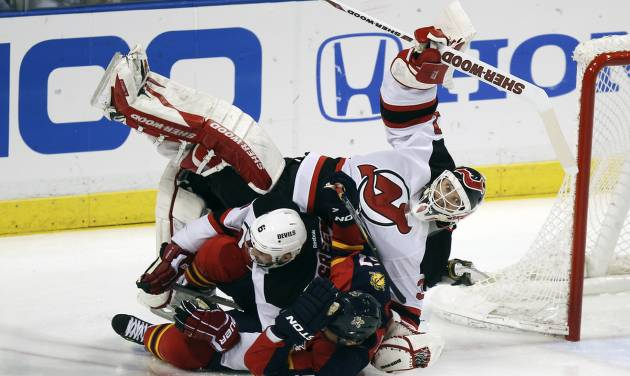 Florida Panthers' Marcel Goc (57) and New Jersey Devils' Andy Greene (6) collide with Devils goalie Martin Brodeur (30) during the first period of Game 2 of an NHL hockey Stanley Cup first-round playoff series in Sunrise, Fla., Sunday, April 15, 2012. (AP Photo/J Pat Carter)