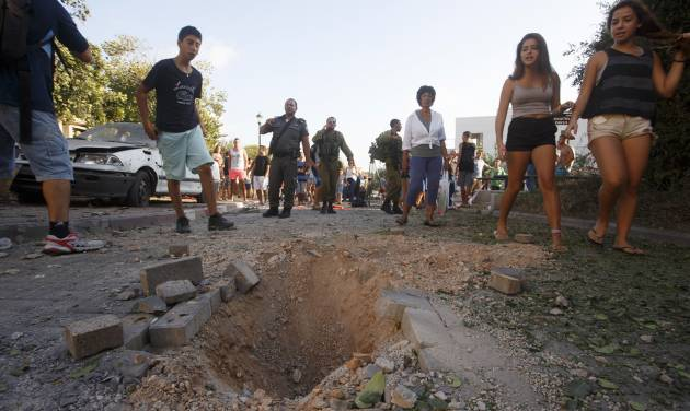 Israelis look at the crater caused by the impact of a rocket fired from Lebanon in kibbutz Gehser HaZiv outside Nahariya in northern Israel, Thursday, Aug. 22, 2013. Military spokesman Lt. Col. Peter Lerner said Thursday that three rockets landed in northern Israel, while one was shot down. (AP Photo/Jinipix)   ISRAEL OUT