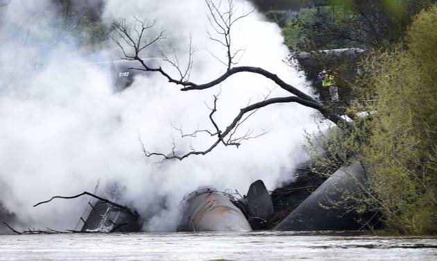 Firefighters and rescue personnel work along the tracks where several CSX tanker cars carrying crude oil derailed and caught fire along the James River in Lynchburg, Va., Wednesday, April 30, 2014. Nearby buildings were evacuated for a time, but officials said there were no injuries and the city on its website and Twitter said firefighters on the scene made the decision to let the fire burn out.  (AP Photo/News & Daily Advance, Autumn Parry)