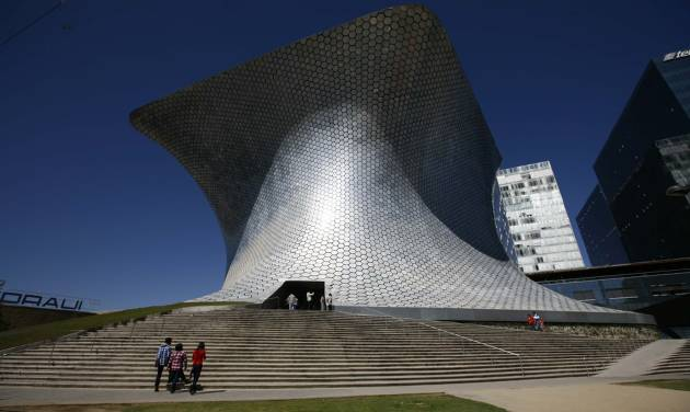 People walk the stairs towards the main entrance to the Soumaya Museum in Mexico City, Monday, Nov. 19, 2012. On the northern edge of Mexico City's Polanco neighborhood, home to gleaming office towers, high-end restaurants and luxury boutiques, billionaire Carlos Slim has erected the mirrored, mushroom-shaped Soumaya museum, home to six floors of Impressionists, Old Masters, Mexican muralists, anonymous Mesoamerican craftsmen and hundreds of other works. The museum is open daily, from 10:30 a.m. to 6:30 p.m. and admission is free. (AP Photo/Marco Ugarte)