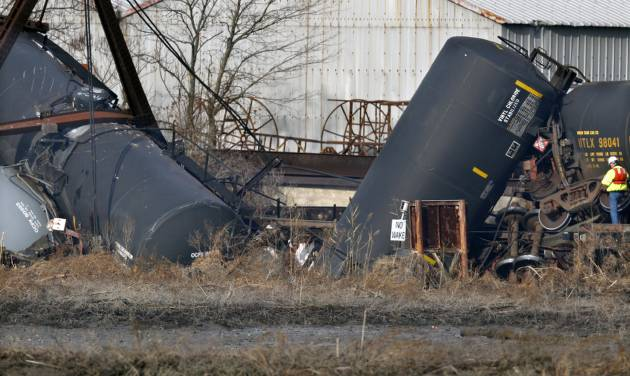 An official stands by derailed freight train tank cars in Paulsboro, N.J., Friday, Nov. 30, 2012. People in three southern New Jersey towns were told Friday to stay inside after a freight train derailed and several tanker cars carrying hazardous materials toppled from a bridge and into a creek. At least one tanker car may contain vinyl chloride, Gloucester County Emergency Management director J. Thomas Butts told WPVI-TV. (AP Photo/Mel Evans)