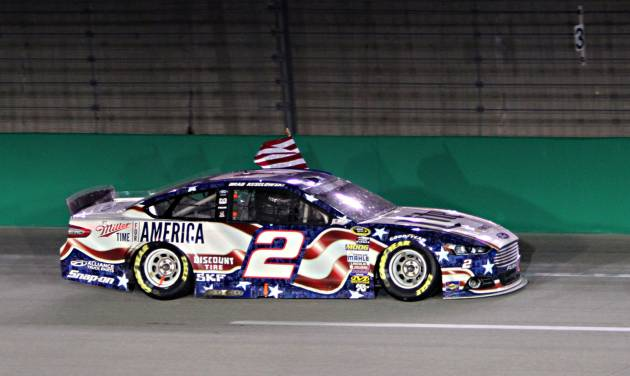 Brad Keselowski takes a victory lap the wrong way in front of the grandstand after winning the NASCAR Sprint Cup series auto race Saturday, June 28, 2014 at Kentucky Speedway in Sparta, Ky. (AP Photo/Garry Jones)