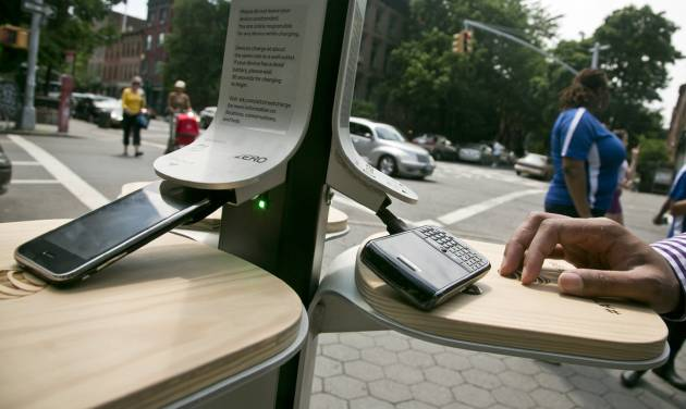 Cellphones powerup with solar energy on Tuesday, June 18, 2013 in New York.  The city has teamed up with AT&T to install 25 solar powered charging stations for public use, available for free in parks and beaches across the five boroughs over the summer.  (AP Photo/Bebeto Matthews)