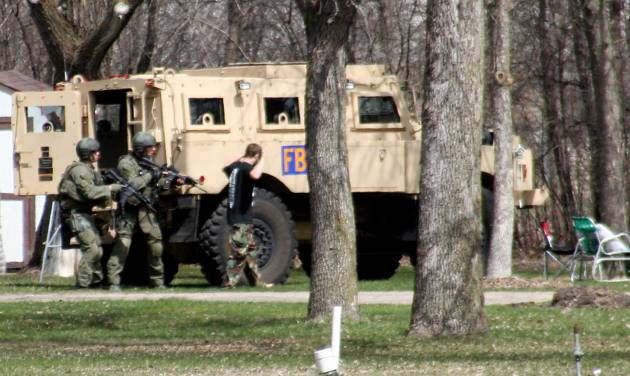 This May 3, 2013, photo provided by Jeremy Jones shows authorities with Buford Rogers, right, during a raid on a mobile home in Montevideo, Minn. Authorities said Monday, May 6, that Rogers was arrested, charged with one count of being a felon in possession of a firearm, and that the agency believes is disrupted a potential terror attack after a search of the home turned up Molotov cocktails, suspected pipe bombs and firearms. (AP Photo/Montevideo American-News, Jeremy Jones) MANDATORY CREDIT