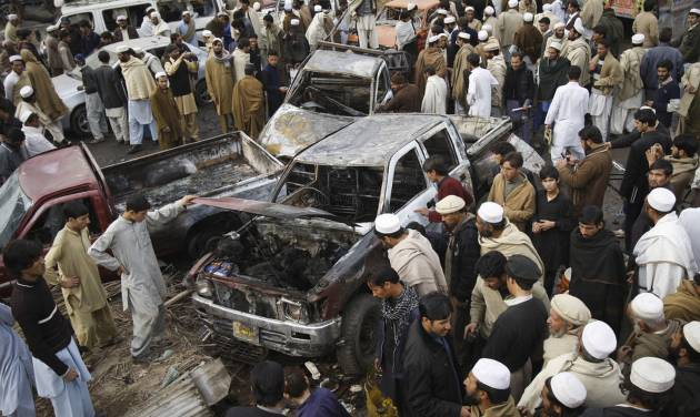 People look at damaged vehicles after a  bomb blast in the Pakistani tribal area of Khyber, Monday, Dec. 17, 2012. A car bomb exploded outside the women's waiting area of a government office in Pakistan's troubled northwest tribal region, killing many  people and wounding others, government officials said. (AP Photo/Mohammed Sajjad)