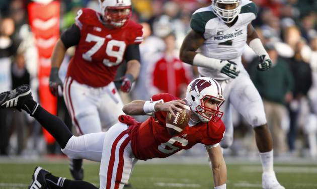Wisconsin quarterback Danny O'Brien stumbles during the second half of an NCAA college football game against Michigan State on Saturday, Oct. 27, 2012, in Madison, Wis. Michigan State won 16-13 in overtime. (AP Photo/Andy Manis)