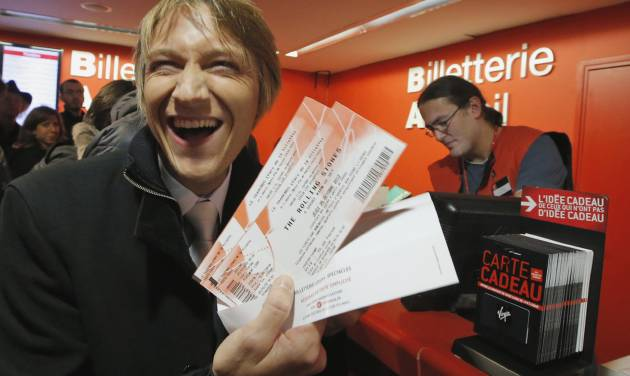 """Michael Evanno, 31, shows the tickets he bought for the Rolling Stones concert at Virgin Megastore in Paris, Thursday Oct. 25, 2012. The Rolling Stones announced a surprise """"warm-up gig"""" in Paris, and within an hour the Champs Elysees was swarming with fans hoping to get satisfaction with one of the 350 tickets for the Thursday night show. (AP Photo/Francois Mori)"""
