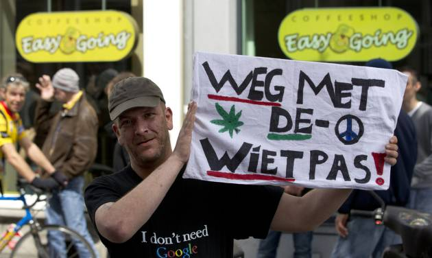 "A demonstrator holds a sign reading ""get rid of the weed pass"" outside coffeeshop Easy Going in Maastricht, southern Netherlands, Tuesday May 1, 2012. A policy barring foreign tourists from buying marijuana in the Netherlands goes into effect in parts of the country Tuesday, with a protest planned in the southern city of Maastricht. Weed is technically illegal in the Netherlands, but it is sold openly in small amounts in designated cafes under the country's famed tolerance policy. The government has said that as of May 1, only holders of a ""weed pass"" will be allowed to purchase the drug, and nonresidents aren't eligible. (AP Photo/Peter Dejong)"