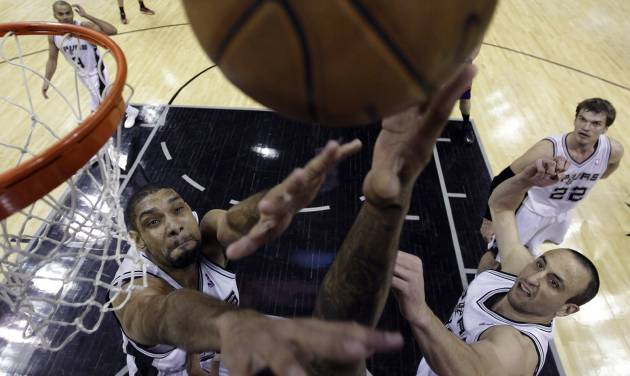 Phoenix Suns' P.J. Tucker, unseen with hand at center, reaches for the ball between San Antonio Spurs defenders Tim Duncan, left, and Manu Ginobili, right, of Argentina, during the first half of an NBA basketball game, Wednesday, Feb. 27, 2013, in San Antonio. Spurs' Tiago Splitter (22) watches.  (AP Photo/Eric Gay)