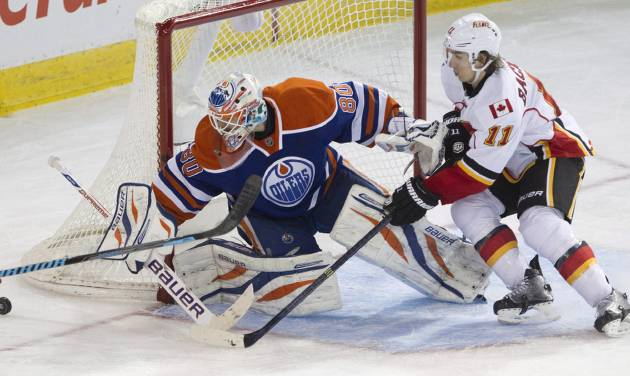 Calgary Flames' Mikael Backlund (11) is stopped by Edmonton Oilers goalie Ilya Bryzgalov (80) during third period NHL hockey action in Edmonton, Alberta, on Saturday March 1, 2014.  (AP Photo/The Canadian Press, Jason Franson)