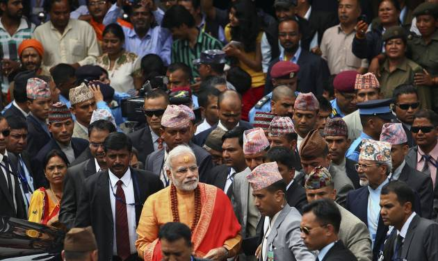 Indian Prime Minister Narendra Modi, foreground in saffron clothing, leaves after his visit at the Pashupatinath Temple in Katmandu, Nepal, Monday, Aug. 4, 2014. Modi flew to the neighboring Himalayan nation Sunday to meet top leaders, offer prayers at a revered Hindu temple and address the parliament. (AP Photo/Kiran Panday)